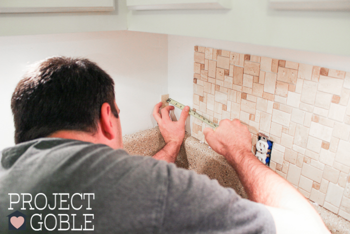 Measure Twice, Cut Once! Jay from ProjectGoble working on peel and stick DIY Kitchen Backsplash
