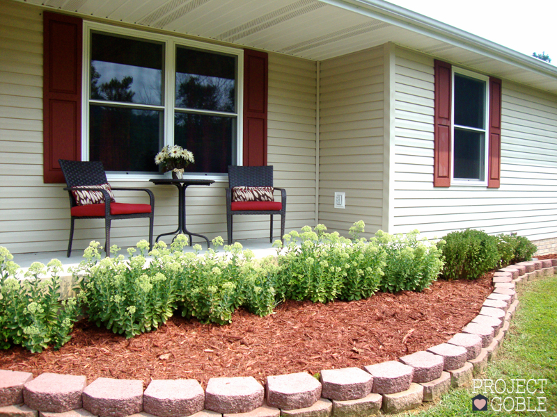 Curved flower bed outside of beige house with burgundy shutters and cute brown and red porch furniture.